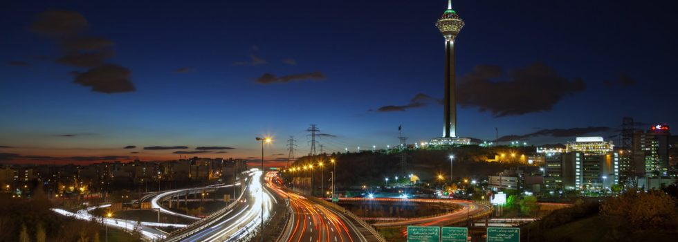 TEHRAN, IRAN - DECEMBER 4, 2015: Illuminated Milad Tower behind highways of Tehran filled with passing cars. Milad Tower is the second most important landmark of Tehran, after Azadi Monument.